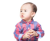 Asian baby holding toy block and looking aside Royalty Free Stock Images