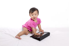 Asian baby with ipad. Asian baby/toddler playing with iPad. Happy and laughing. Shows learning at a young age Royalty Free Stock Photos