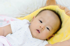 Asian baby laying on bed, just woke up Stock Photography