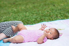 Asian baby laying down on ground at park Royalty Free Stock Photo