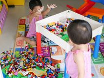 Asian baby left is cleaning up toys she played with her little sister royalty free stock photo