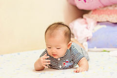 Asian baby lie prone on bed. Cute Asian baby lie prone on bed Royalty Free Stock Photography