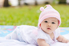 Asian baby lie prone on ground at park. Cute Asian baby lie prone on ground at park Stock Photos
