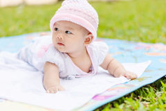 Asian baby lie prone on ground at park. Cute Asian baby lie prone on ground at park Royalty Free Stock Image