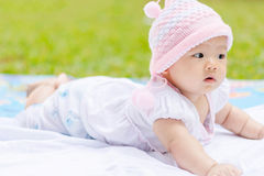 Asian baby lie prone on ground at park. Cute Asian baby lie prone on ground at park Royalty Free Stock Images
