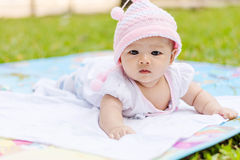 Asian baby lie prone on ground at park. Cute Asian baby lie prone on ground at park Stock Image