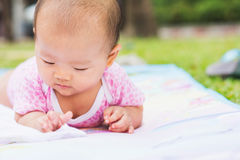 Asian baby lie prone on ground at park Stock Photo