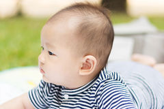 Asian baby lie prone on ground at park. Cute Asian baby lie prone on ground at park Stock Images