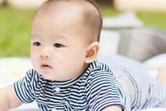 Asian baby lie prone on ground at park. Cute Asian baby lie prone on ground at park Royalty Free Stock Photos