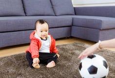 Asian baby looking at football Royalty Free Stock Photography
