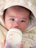Asian baby milk feeding silently with headgear. Milk bottle holding by adult hand stock photo