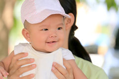 Asian baby in a mom hand and smile with happily. Asian baby in a mom hand and smile with happily,concept of health and development of the children Stock Image