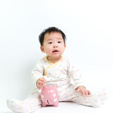 Asian baby with piggy bank. Portrait of Asian baby with piggy bank Royalty Free Stock Image