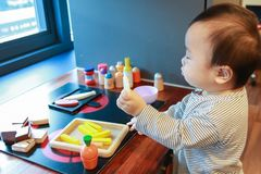 Asian baby playing alone with toy kitchen kit stock photos