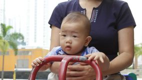 Asian baby playing on seesaw stock video footage