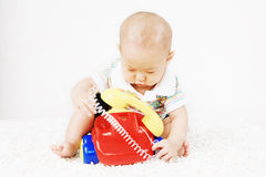 Asian Baby Playing With Telephone Stock Photo