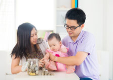 Asian baby putting coins into the glass bottle with help of pare Stock Images