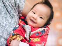 Asian Baby with red costume for Chinese new year. New born Asian baby girl, 4 months old, with traditional red Chinese Cheongsam or qipao costume with smile royalty free stock image