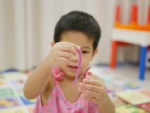 Asian baby`s hand holding a stripe of play dough she made. Selective focus of Asian baby`s hand holding a stripe of play dough she made royalty free stock images