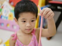 Asian baby`s hand holding a stripe of play dough she made. Selective focus of Asian baby`s hand holding a stripe of play dough she made stock photography