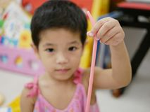 Asian baby`s hand holding a stripe of play dough she made. Selective focus of Asian baby`s hand holding a stripe of play dough she made royalty free stock image