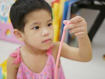 Asian baby`s hand holding a stripe of play dough she made. Selective focus of Asian baby`s hand holding a stripe of play dough she made stock photos