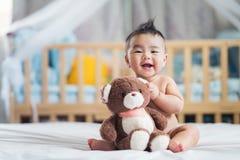 Asian baby sit with teddy bear stock photos