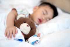 Asian baby sleep with teddy bear and saline on the bed in Hospital royalty free stock images