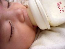Asian baby sleeping milk feeding,nipple in mouth. Asian  baby milk feeding  falling into sleep,nipple stuck in mouth,bottle full of bubbles Royalty Free Stock Photos