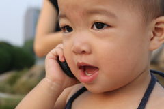 Asian baby in sling suit,murmuring to a cellphone royalty free stock image