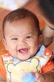 Asian baby smiling happily and have bottle of milk in hand. Asian baby smiling happily and have bottle of milk in hand,concept of health and growth Royalty Free Stock Images
