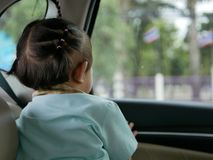 Asian baby girl enjoy looking at a Thai national flag outside of the car window stock image