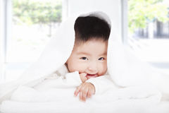 Asian baby sucking  finger under  blanket or towel Royalty Free Stock Images