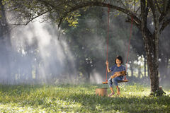 Asian baby  on swing with puppy. Royalty Free Stock Image