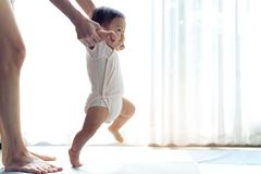 Asian baby taking first steps walk forward on the soft mat. royalty free stock photos