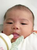 Asian baby tongue sticking out tasting milk Stock Image