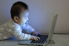 asian baby working with laptop stock photography