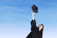 Asian bachelor throwing a graduation cap Royalty Free Stock Photography