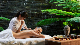 Asian back massage theraphy spa hot stone Royalty Free Stock Photos
