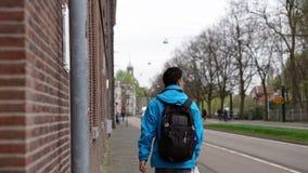 Asian backpacker man walk alone in European city street of Amste Stock Photography