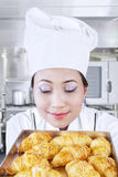 Asian baker smells bread Stock Photo