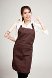 Asian Baker woman  in apron  show OK with wooden rolling pin. On gray background Royalty Free Stock Photos