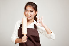 Asian Baker woman  in apron show OK  with wooden rolling pin Royalty Free Stock Image