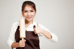 Asian Baker woman  in apron thumbs up  with wooden rolling pin Royalty Free Stock Photos