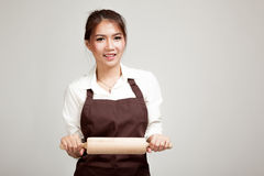 Asian Baker woman  in apron  with wooden rolling pin Royalty Free Stock Image