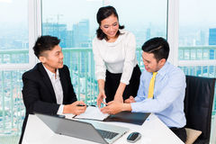 Asian banker counseling man in office Royalty Free Stock Photo