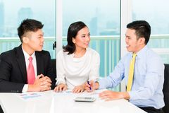 Asian banker selling insurance to couple stock photography