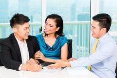 Asian banker selling insurance to couple royalty free stock image