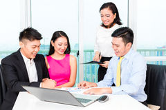 Asian banker team counseling couple in office stock image