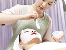 Asian beautician applying facial mask on face of young woman. Asian beautician applying white facial mask with a brush on face of a young woman royalty free stock image